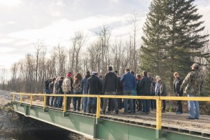 The group stands on the temporary bridge that was built two years ago. A permanent bridge is being constructed and will connect Freedom Road, which will join Hwy. #1 to the west of Shoal Lake 40. (photo credit: James Christian Imagery)