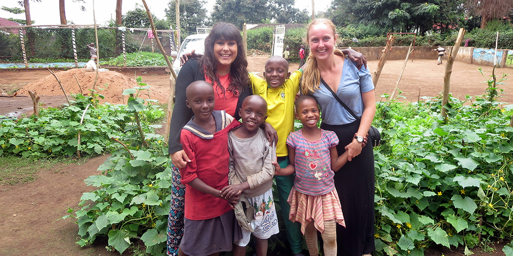 Jenn French (right) stands with fellow volunteer, Karina Rottinger, and some of the children at Msamaria Centre for Street Children in front of the garden they planted to help reduce the food costs of the centre. (Photo courtesy Jenn French)